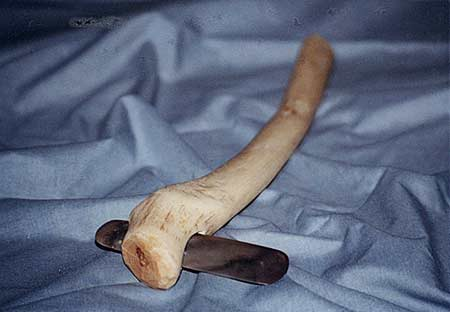 Reconstructed axe-head with a wooden curved handle with a deep groove worn/carved across one end with a flint axe head fitted in. The axe head is cylindrical, long and thin.