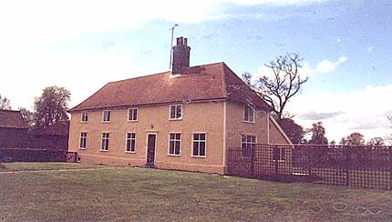 Photograph of Church Farmhouse – a rectangular building covered in ochre coloured plaster with a tiled roof.