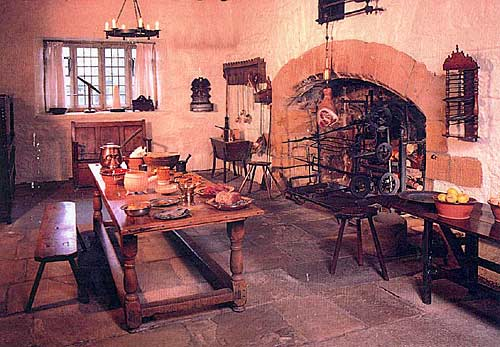 Photograph of kitchen in the hall in the centre of which is a long kitchen work table and behind that a large fireplace with a spit