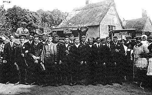 Black and white photograph of young men standing outside the Six Bells public house.