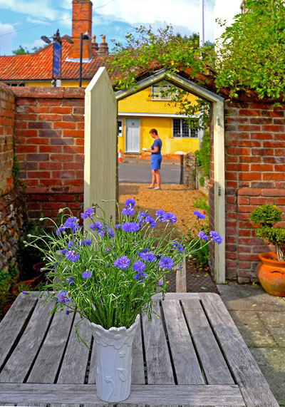 Image of blue cornflowes in white vase on table loooking through open gate in red brick wall out to The Street beyond
