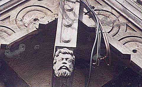 Detail of top point of roof - wooden beams with a wooden carving of a bearded man