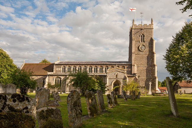 St. Mary's Church in background on sunny evening against blue sky with clouds and with leaning gravestones in foregound