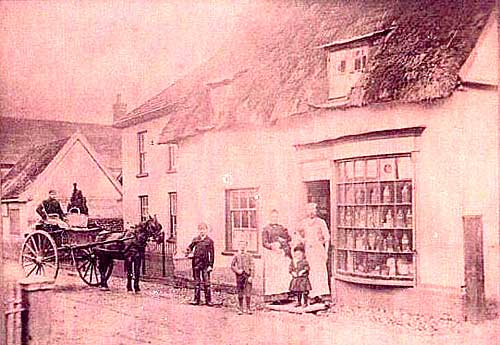 Sepia tinted photograph of The Bakehouse and Bakery complete with multi-paned bow-fronted shop window. The Kenny family are standing outside the shop with their horse and cart used for deliveries.