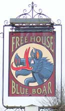 "Free standing pub sign. Above a large circle ""FREE HOUSE"" and below ""BLUE BOAR"". In the circle is the head and shoulders of a strange looking blue boar who has bright red tusks – a slightly fantastical style of drawing."