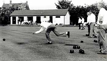 Black and white image of Walsham-le-Willows bowls club member in action with pavilion in backgroung