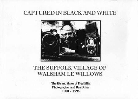 cover black and white image of photographer fred ellis holding his 1940 tick-a watch camera and surrounded by three of his other conventional cameras