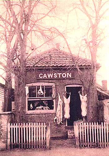 Sepia tinted photograph of Cawstons the butchers - a square brick building with a tiled roof surrounded by a paling fence. Whole carcasses of animals are hanging outside the door and in the window.