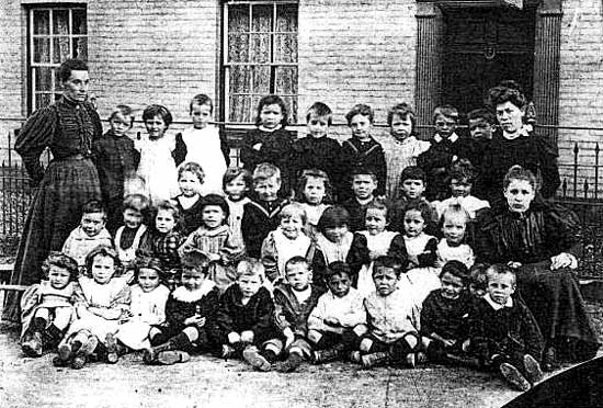 Black and white photograph of thirty-five young children and three adults seated in rows outside the National School.