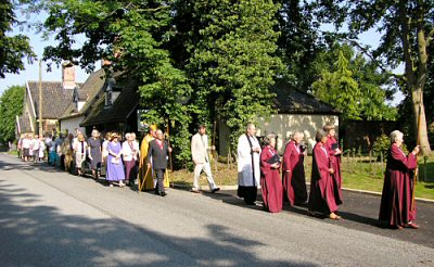 The congregation process to the lychgate and extended cemetery for the consecration ceremony