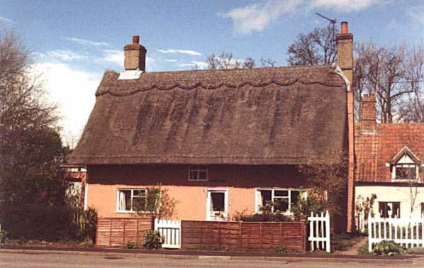 A photograph showing a typical country cottage, a windowless thatched roof with just a hint of a bedroom window peeping out from under the thatch, at the centre of the wall. Light pink painted walls, white woodwork, perfect!