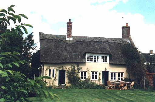 "The back of the cottage which boasts a thatched roof with an ""eyebrow"" over a pair of windows. The back of the house has two doors and there is a garden table and chairs."
