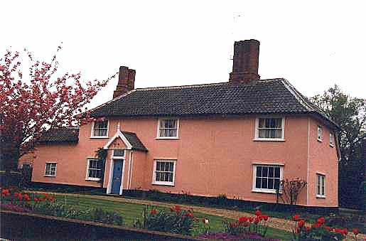 A photograph of a pink building taken from the front and shows a tiled roof and two good chimneys. There is a central porch and white painted windows.
