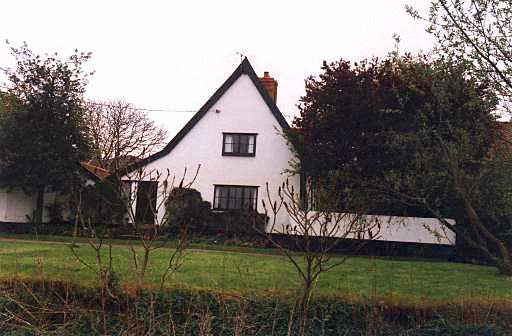A white painted house, taken from in front of the house which is built end-on to the road. It has a steep tiled roof.