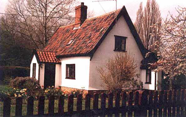 An angled photograph of a small cottage with a tiled roof above white painted walls, with the front wall to the left, showing a small porch which contains the front door, another charming cottage.
