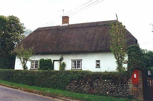A thatched farmhouse, no dormer windows and with the walls painted white. The photograph was taken at an angle showing both the right hand end of the house and also the front face, which is to the left and contains the front door.
