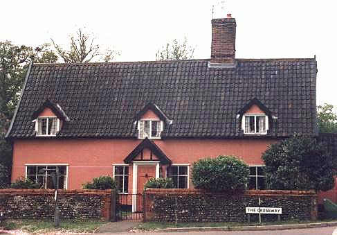 A photograph of a very nice looking cottage taken from directly in front, it has a tiled roof with three dormer windows and the walls are painted pink. There is a front porch.