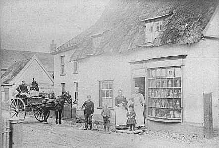 An old black and white photograph showing a building with a thatched roof with two dormer windows, and it shows a bow window. There are people outside, and also a pony pulling a Tumbrel.