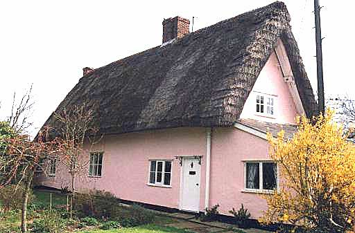 An angled photograph of a pink painted thatched farmhouse showing a small extension on the end facing the camera, and with an entrance door located in the front wall, just around the corner of that extension.