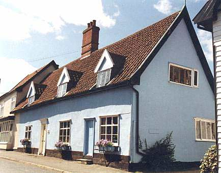 A colour photograph of a cottage with a high pitched tiled roof which has three dormer windows. The house is painted pale blue.