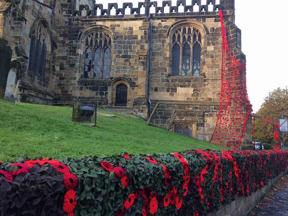 Knitted poppies draping church wall