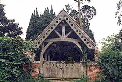 Colour photograph of the lych gate showing carved roof and gate.