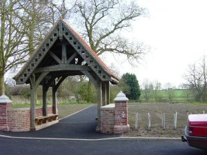 Image of the newly resited lychgate, and Oak framed gatewayto a churchyard