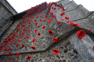 Knitted poppies affixed to a fine almost invisible net and draped from the top of St Mary's church tower viewed from the base of the tower looking up, covering the whole of the porch wall at the base.