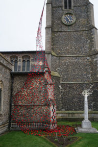 Knitted poppies affixed to a fine net and draped from the top of St Mary's church tower showing the wisp of almost invisible net starting at the top and widening as it falls down the tower covering the whole of the porch wall at the base.