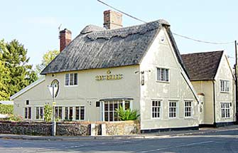 "A cream coloured thatched two story building on the corner of one part of the crossroads. Gold lettered sign on side ""Six Bells""."