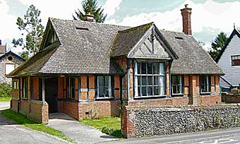 oak-framed, red brick building with more roof than wall and a tall thin chimney with texts carved into the timber