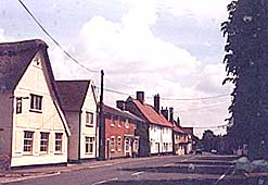 Colour image of main street in Walsham, 1984, now with tarmac road