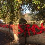 church wall draped with knitted poppies