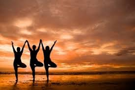 Image of three people in yoga pose on a beach in silhouette against a wonderful sunset illuminating clouds in the sky