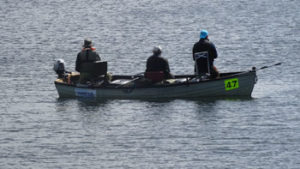 three men in a boat on chew lake