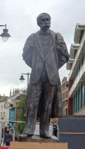 Statue of Edward Elgar against a gloomy sky