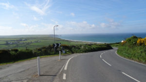 Image bright sunny day, blue sky, looking down a winding road to newgale strand and the sea