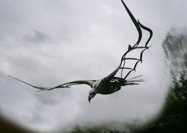 Cast iron bird of prey with large wing span and eagle like head and beak, wings spread in full flight against a grey cloudy sky.