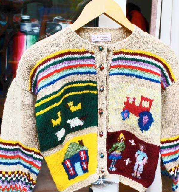A knitted cardigan depicting four images, two each side to the middle and bottom of the garment of a red tractor, a blue house, sheep and two human figures. Across the top of the cardigan from arm to arm are coloured lines giving the impression of a rainbow. The ends of the sleeves are tinged with a similar pattern and well as a chequerboard pattern in the same colours.