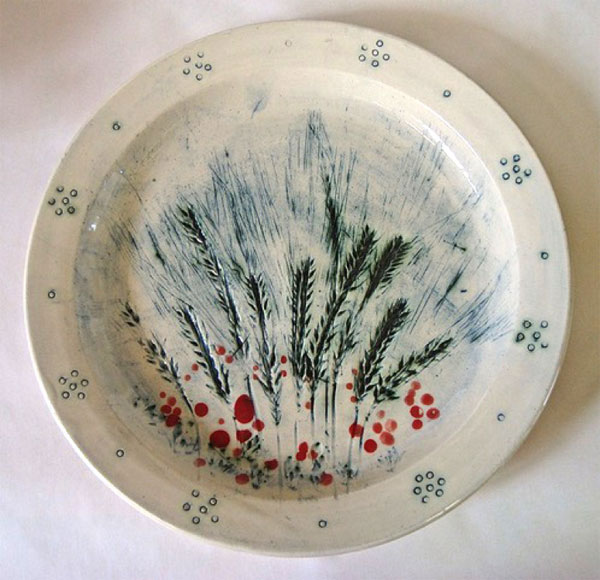 Cream coloured plate with definite rim decorated in red and green giving the impression of wheat spears and red poppies.