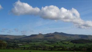 Image of Brecon Beacons on a clear day with blue sky and white clouds in the sky