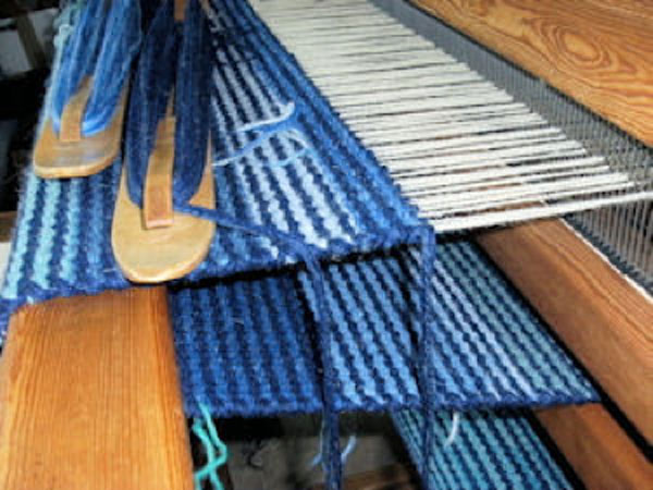 An image of wool in various shades of blue through to a light cream in the process of being woven on a loom into a rug.