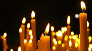 lit candles against a dark black background