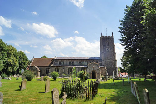 Photograg of St. Mary's Church, Walsham-le-Willows on sunny day, set against blue sky with coulds and the sunlit cemetary in the foreground