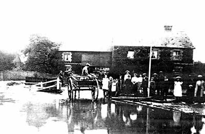 """Very old photograph showing a horse and cart proceeding through flood water, whilst being watched by some 16 people in front of an old building that has a sign bearing the name """"H. POLLARD""""."""