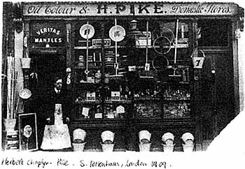 "Old photograph showing the outside of Herbert Prike.s shop in London and this shows Herbert in the shop doorway with all manner of goods displayed both inside and outside of the windows. The sign above the shop reads ""Oil Colour & - H.PIKE. - Domestic Stores"" and written in hand-writing on the bottom of the photo ""Herbert Chapyr – Pike . S. Tottenham, London 1909."""