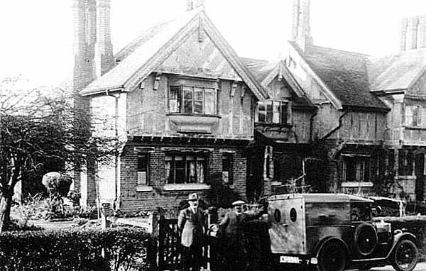 An old balck and white photograph showing two men with an old bakers van which is shaped rather like a box on wheels (has spare wheel attached to the driver's door). In the background is a slightly angled view of the South cottages – overhanging upper floor several tallish chimneys.