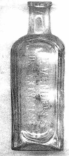 Photograph of an old imperfectly shaped, glass bottle, possibly a chemist's bottle with straight sides and round shoulders topped with a round straight neck suitable for a cork. The front panel has raised  wording.