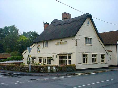 Modern photograph of the Six Bells Public House taken from outside 'Sweetbriars'. A cream coloured thatched two story building on the corner of one part of the crossroads.