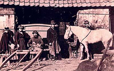 A sepia photograph showing five members of the Stevens family outside Dages with their white horse looking on. The 3 men all have beards and, along with the 2 women they are all dressed in old fashioned clothing – all are wearing hats of various sorts all beneath a pan-tiled roof of a out building which contains a horse cart.